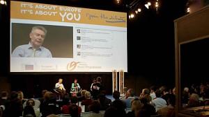 Foto van de sprekers in het debat met Karel De Gucht ondersteund door simultaanvertaling