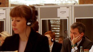 Picture of attendees listening to simultaneous interpretation tips with interpreter booths in the background